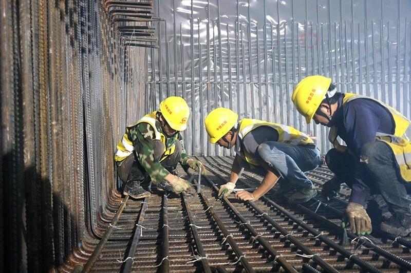 广州地铁13号线二期六标彩纪区间E21#盾构井,数名工人正在进行横通道二衬底板钢筋绑扎,全力打好工序转换攻坚战.JPG